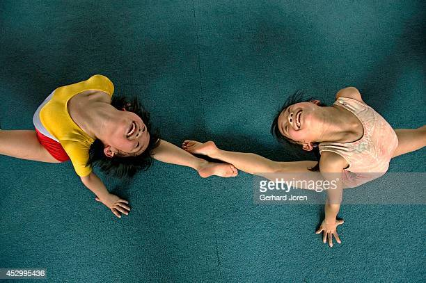Two young girls stretch their backs during a gymnastics training session in Guangzhou China