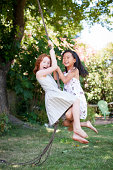 Two young girls swing together
