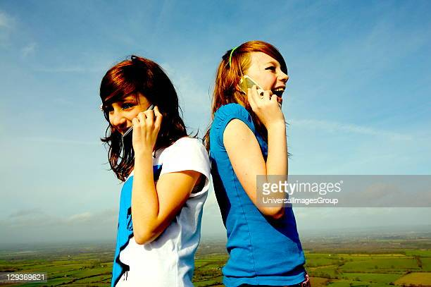 Two young girls talking and laughing on mobile phones in a field