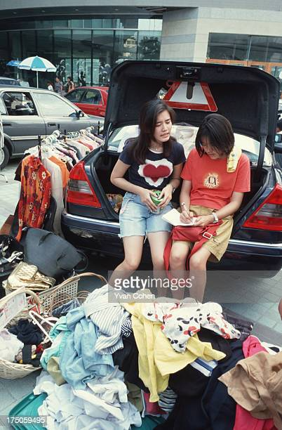 Two young girls wait for customers as they sell goods from the car boot of their mercedes benz Many Thais have resorted to selling goods on the...
