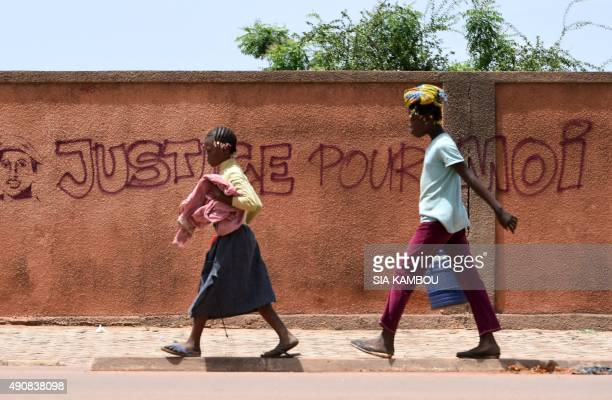 Two young girls walk past a wall with graffiti reading 'Justice for me' in Ouagadougou on October 1 2015 General Gilbert Diendere the leader of...