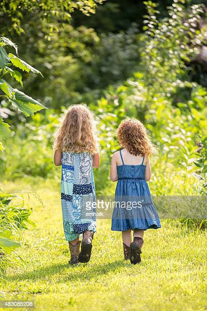 Two Young Girls Walking In Dresses & Cowboy Boots