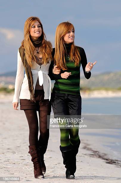 Two young girls walking on beach.
