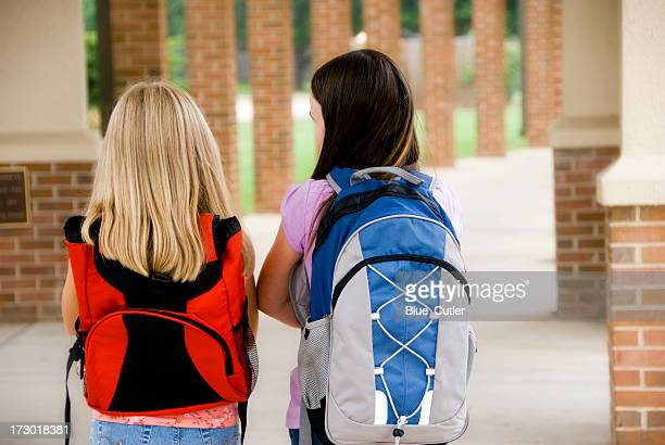 Two young girls walking to school