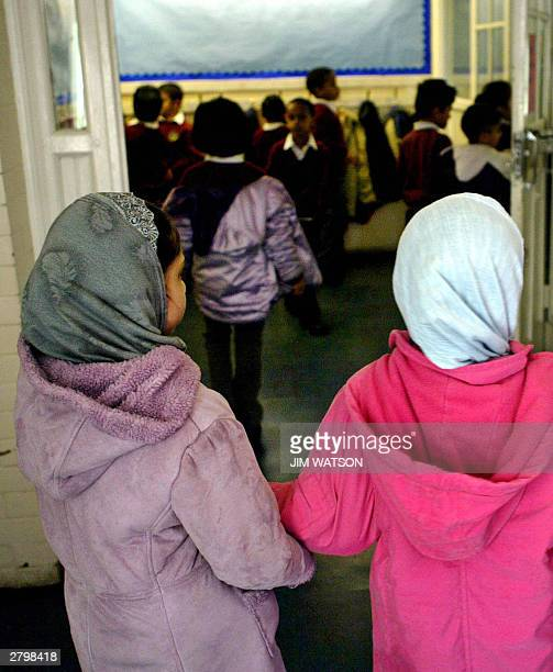 WITH 'RELIGIOUS EDUCATION A FESTIVAL OF LIGHT IN BRITAIN' Two young girls wearing muslim headscarfs walk handinhand into the main entrance of...