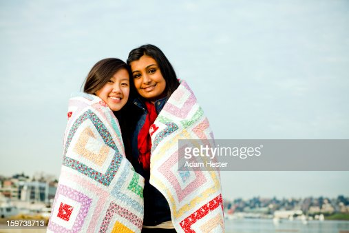 Two young girls wrapped in a quilt outside. : Stock Photo
