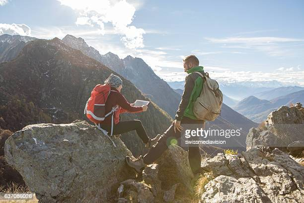Two young hikers on mountain top looking at digital tablet