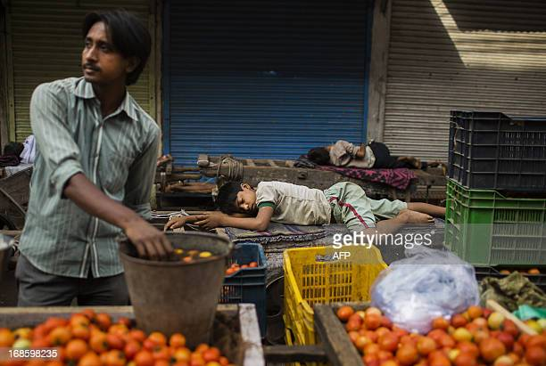 Two young Indian labourers sleep on hand carts as a vegetable vendor looks on in the Old Quarters of New Delhi on May 12 2013 The Indian government...