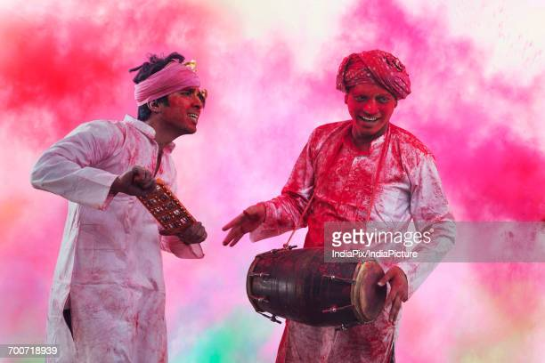 Two Young Indian men With Colored Face Dancing During Holi Color festival