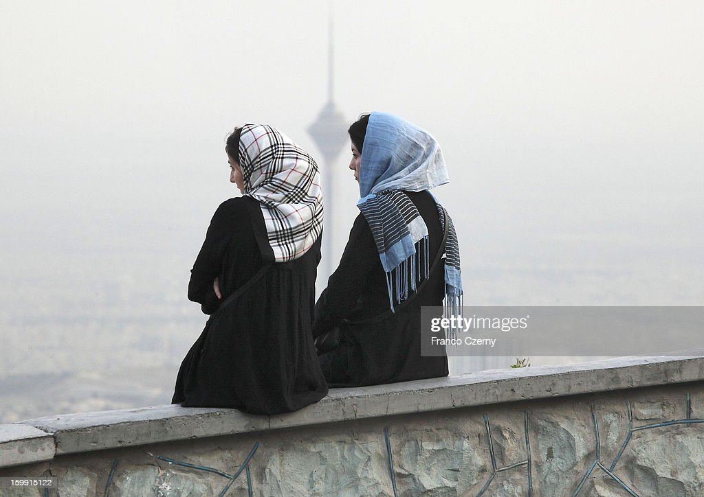 Two young iranian women in Tehran, Milad Tower in background on August 28, 2012 in Tehran, Iran.