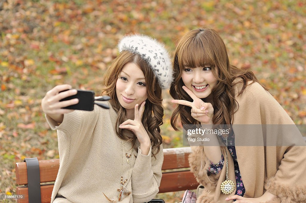 Two young is taking photos on a smartphone : Stock Photo