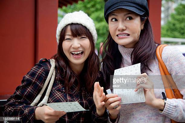 Two young Japanese women with good and bad fortune papers
