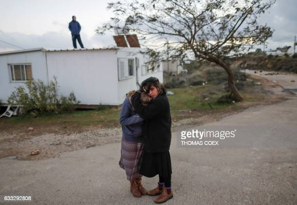 TOPSHOT Two young Jewish settlers embrace as Israeli security forces evict hardline residents from the wildcat Amona outpost northeast of Ramallah on...