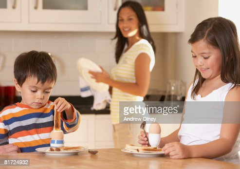Two young kids in kitchen eating eggs and toast with woman in background smiling : Stock Photo