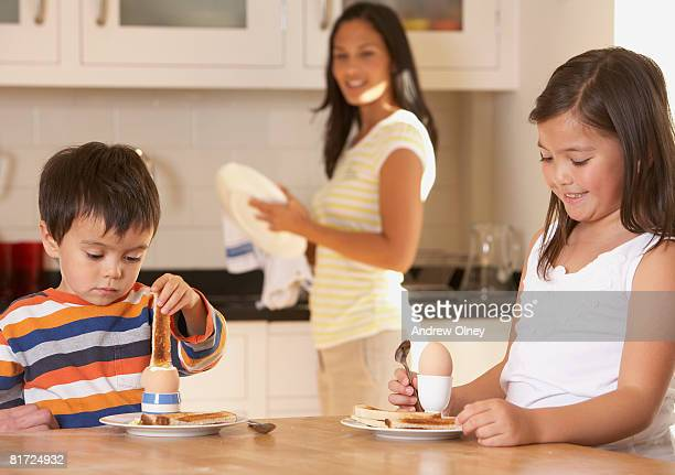 Two young kids in kitchen eating eggs and toast with woman in background smiling