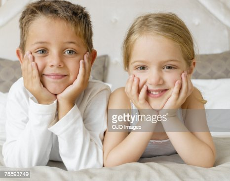 Two young kids lying on their stomachs smiling : Stock Photo
