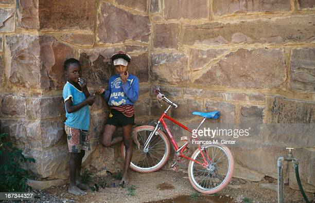 Two young kids stand next to a bike on a village street in city of Kolmanskop Namibia September 1995
