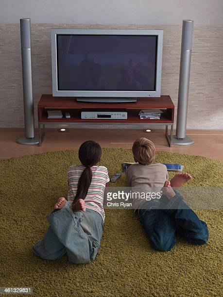 Two young kids watching the television