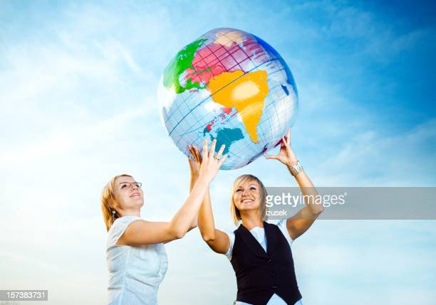 Two young ladies holding up inflatable globe