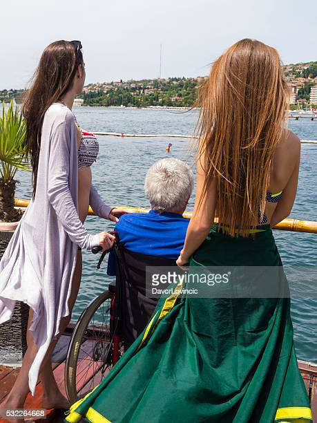 Two young ladies with disabled senior in wheelchair