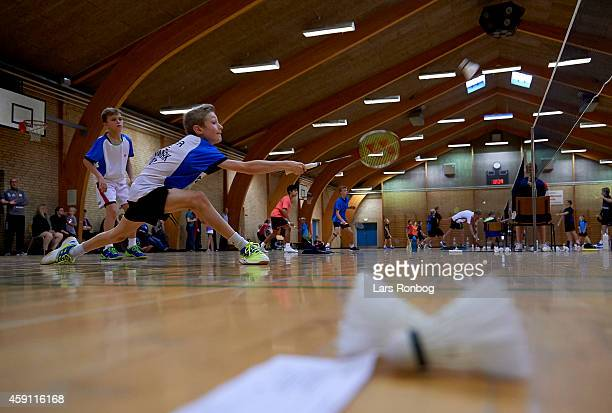 Two young male badminton players in action with a shuttlecock and the scoreboard paper lying on the the court during the Yonex Denmark Junior Youth...