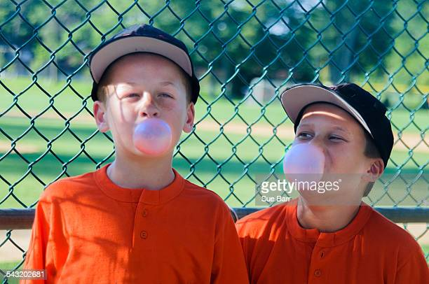 Two young male baseball players blowing bubbles with bubblegum
