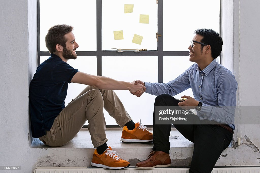 Two young male creatives shaking hands : Stock Photo