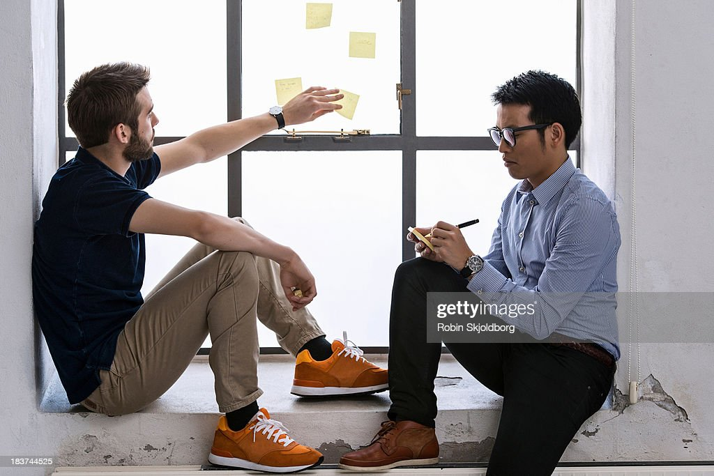 Two young male designers sharing ideas on post it notes : Stock Photo