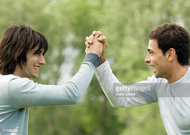 Two young male friends giving each other special handshake