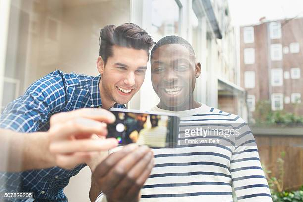 Two young male friends taking selfie behind patio glass