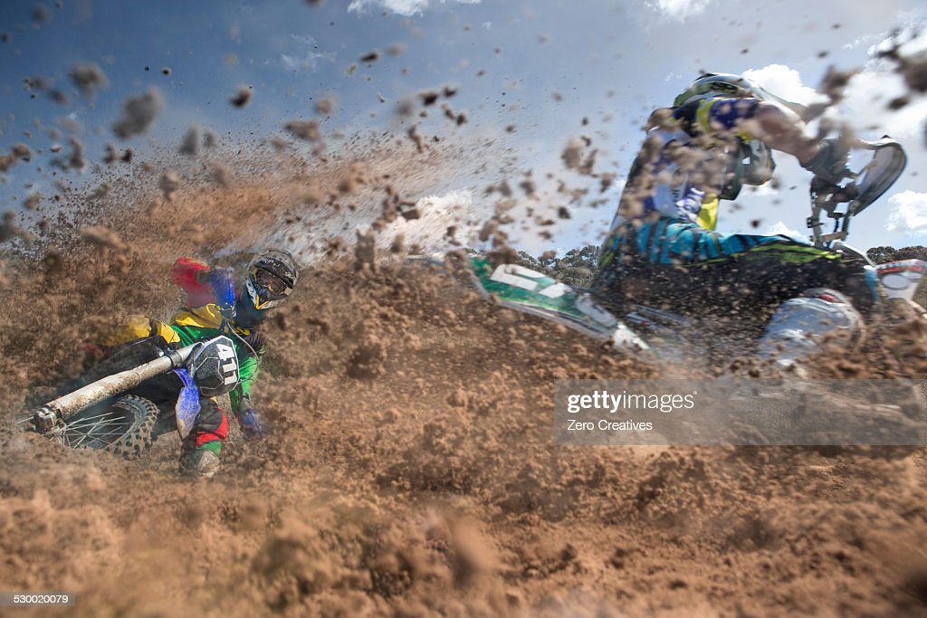 Two young male motocross riders racing through mud