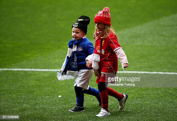 Two young mascots for Liverpool FC and Everton FC walk hand in hand across the pitch before a memorial service to mark the 27th anniversary of the...