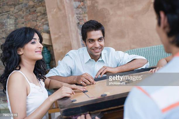 Two young men and a young woman playing carom
