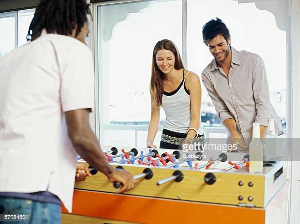 Two young men and a young woman playing foosball
