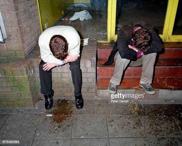 Two young men are sick on the pavement of Union Street on a night out in Plymouth November 2001