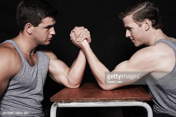 Two young men arm wrestling, side view