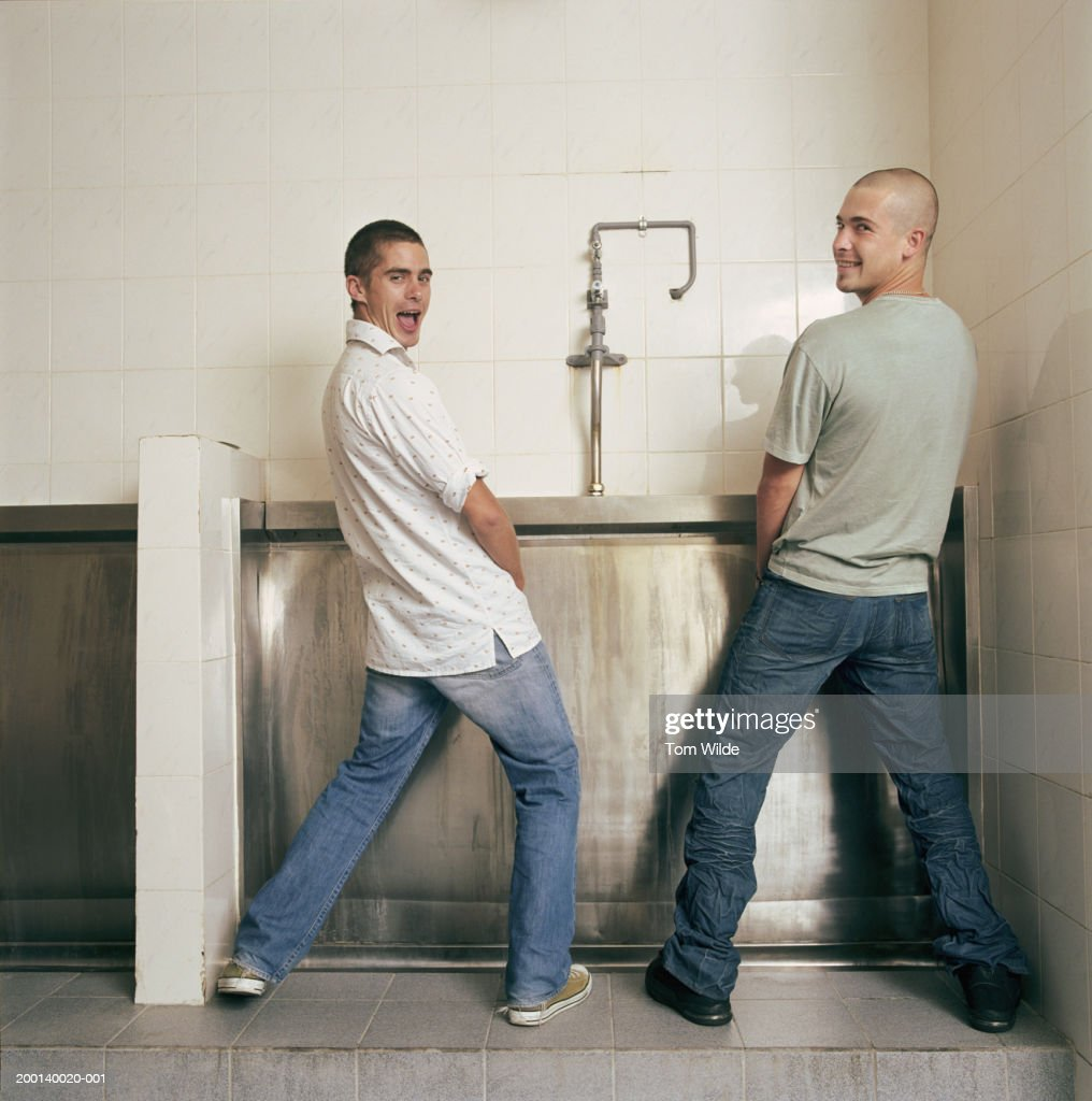 Two young men at urinal, looking over shoulders, portrait