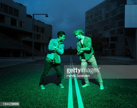 two young men challenging each other in the street : Stock Photo