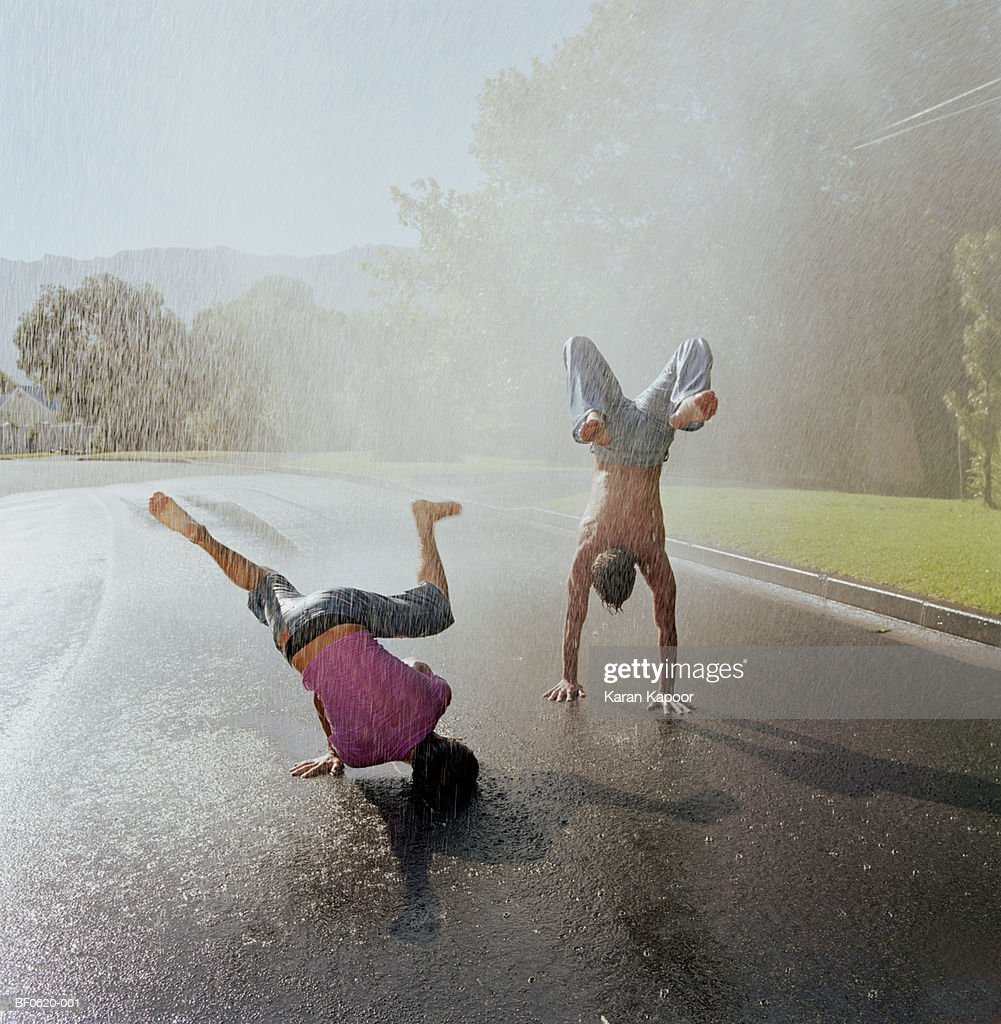 Two young men doing handstands in rain : Stock Photo