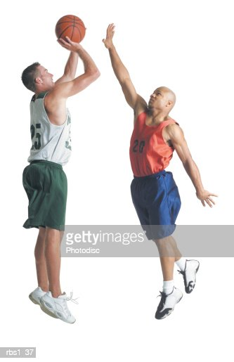 two young men dressed in opposing team basketball uniforms are jumping up while one prepares to shoot a basketball and the other tries to block it