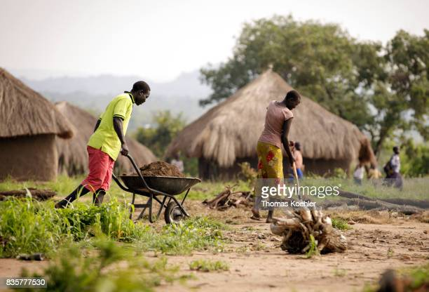 Two young men farm a field at the Rhino Refugee Camp Settlement in the north of Uganda The area is home to about 90000 refugees from South Sudan on...