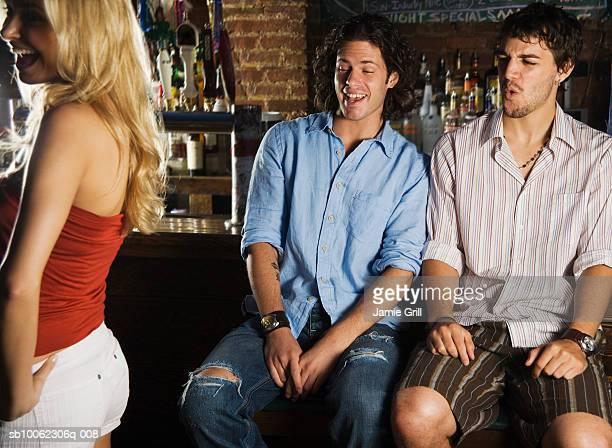 Two young men flirting woman in bar