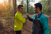Two young brunette men giving high five, shaking hands after sports, exercise, jogging, trekking or running in the forest. Close friends holding their hands and smiling to each other. Celebrating thei