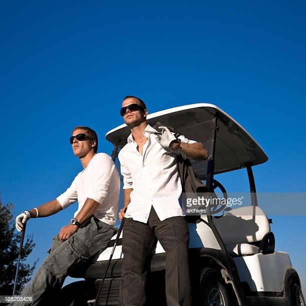Zwei junge Männer Golfer sich auf Golfwagen
