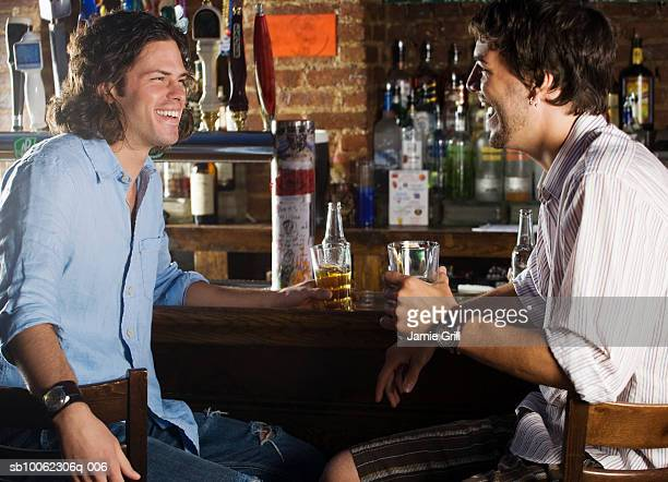 Two young men having drink in bar, smiling