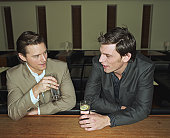 Two young men having drinks leaning on bar