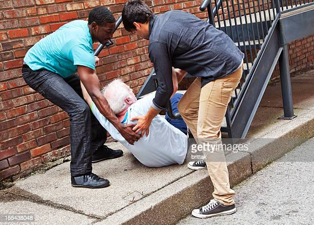 Two young men help an elderly man get back up after falling