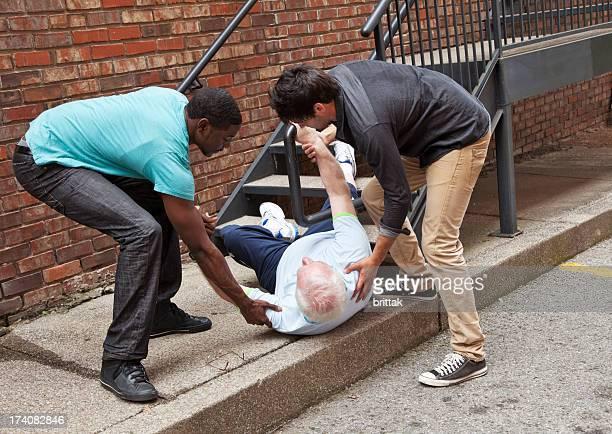 Dois homens jovens ajudando a baixar para baixo sénior. Multi-étnico