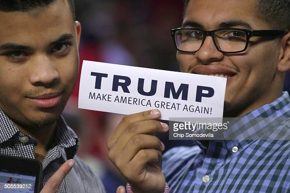 Two young men hold up a bumper sticker which says 'Trump Make America Great Again' before the Republican presidential candidate delivers the...