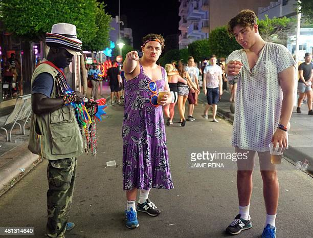 Two young men in women's costumes pose in Punta Ballena street in Magaluf holiday resort in Calvia on the Spanish Mallorca Island on July 19 2014...